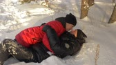 wintertime : Man and woman having fun in winter forest. Joyful husband and wife fell on the snow and kissing each other in the winter forest. Slow Motion Stock Footage