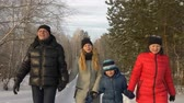 cuatro estaciones : Friendly family holding hands and walking in snowy forest at cold winter day. Happy family mom, dad, son and daughter walking together at snowy cold day in winter forest