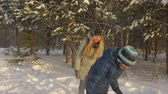 wintertime : Cheerful boy and girl teenager playing in snowballs in snowy forest at winter vacation. Happy teenager playing in snowball fight in winter forest at Christmas vacation. Winter activity and leisure Stock Footage