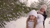 wintertime : Daughter walking together mom in snowy forest at frosty winter day close up. Daughter leading mother through winter forest and snow falling from tree branches Stock Footage