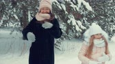 страна чудес : Happy mom and daughter dancing front camera on winter trees background while snowfall. Cheerful daughter together mom having fun and dancing at winter walk in snowy forest