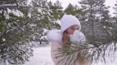 hoarfrost : Frozen teenager girl while snowfall in winter forest while walking hiking in cold and frosty day. Cheerful girl teenager warming in snowy forest because frozen while walk Stock Footage