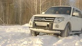 к северу : SUV car driving on snowdrift at winter road on snowy forest background slow motion. Off road car driving on road while winter trip in snowy forest Стоковые видеозаписи