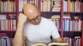 estante : Bald man holding head and reading book at table in home library on bookcase background. Thoughtful man in glasses reading scientific literature in university library Vídeos