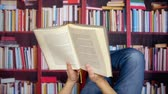 conferencista : Man reading old book. Close up view man reading a book in the library, while lying in front of bookshelves. Stock Footage