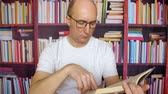 nobre : Thoughtful white man read book at bookshelf background in library interior. Man in glasses and white t-shirt sits at desk table and thinking with book. Close up portrait serious male face in glasses
