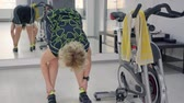 interval : London, UK - March 12, 2019: Woman bends down to stretch the muscles of the legs. Stretching exercise in GYM cyclinf class