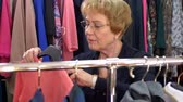 halenka : Portrait of happy senior blonde woman in glasses is shopping choosing a blouse in a clothing store, front view.