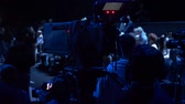 mass media : Videographer shooting video for television show in studio. Cameraman taking video streaming at event. Mass media and television, film production concept. Low key light Stock Footage