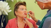 nyugdíjas : Elderly woman is painting her friends lips for the party with bright pink lip gloss. Make up senior adult aged woman