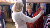 間違った : Stylists, two women, criticize the choice of an elderly blonde womans dress in the store, helping her choose suitable clothes. 動画素材