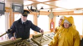 peaked : Elderly grey-haired captain of the Norway ship in the wheelhouse is talking with his team of sailors and workers in yellow raincoats and gives them instuctions.