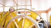 nyugdíjas : Senior woman in yellow raincoat rotates the steering wheel on the ship. Tour in the wheelhouse of the marine vessel.