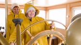 akce : Smiling woman captain turning steering wheel floating ship. Female captain of sailing ship steering helm on navigation ship. Sailing and shipping concept