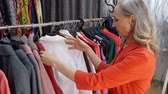 nyugdíjas : Gray haired elderly woman choosing dress in fashionable clothing store. Elegant woman choosing clothes in new fashion collection in showroom. Female shopping concept