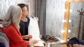 halenka : Mature woman choosing white blouse front mirror in showroom. Fashion stylist helping adult businesswoman trying white shirt in clothing store. Shopping concept