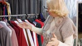 racks : Elderly blonde woman is choosing clothes in clothing shop. She takes clothes off the rack and looks at them talking with seller. Shopping concept.