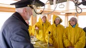 denizci : Elderly grey-haired captain of the Norway ship in the wheelhouse is talking with his team of sailors and workers in yellow raincoats. He gives them instructions before trip. Stok Video