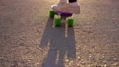 planche à roulettes : Teen girl in white sneakers is riding on plastic skateboard pushing herself on asphalt road in slow motion. Small penny board for kids. Outdoor street sport and activity. Slow motion backlit sun light Vidéos Libres De Droits