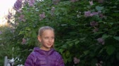 lilás : Portrait of child girl in purple jacket with ponytail is walking along the lilac bush in city park in early spring.