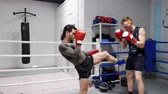 coachen : Fighter men in boxing gloves training punches on ring in sport club. Boxer man training kicks to body with personal coach in fight club. Boxing exercise