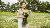 pihy : Happy laughing child girl in white summer dress is walking on glade. She is with bouquet and wreath of daisies on flower meadow. Teen girl with long hairs and freckles on her face.