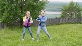 Playful teenager girls dancing on green meadow on forest and river landscape. Carefree girl teenagers having fun while summer vacation in countryside
