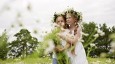 Two girl teenager in floral wreath with flowers bouquet standing on blooming field. Romantic girls with flower bouquet on camomile field at summer day Vidéos Libres De Droits