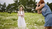 Teen girl is posing and looking at camera on photo shoot. Mom takes pictures of her daughter in white dress with daisy wreath on her head in flower meadow. Nature shot for child girl.