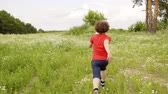 Young boy running to girl on green field. Children playing in catch up on flower meadow. Having fun on summer vacation