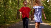irmãs : Two girlfriends holding hands walking in summer park. Happy teenager girls walking on park path at summer day. Frienship concept. Summer vacation