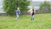 Having a fun time in countryside. Two teen girls making acrobatic cartwheel on lawn walking on nature together. Beautiful foresr and river background. Children sport outdoor activities.