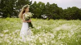 Girl is standing on flower glade looking at camera and smiling. Cute teen girl in white dress with wreath on head and bouquet of daisies at flower meadow. She is posing at shoot. Windy summer day. Vidéos Libres De Droits