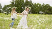 Summer outdoor ativities for children at vacation. Two teen girls with flower wreaths play in meadow hold hand and spinning around. Have a fun time on nature. Walking with friend, friendship.