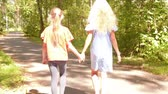 achteraanzicht : Frends walking in park, children friendship. Two teen girls walks in nature park holding hands in light of setting sun, back view. Summer vacation.