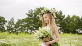 Portrait of beautiful girl is standing on flower glade with closed eyes. Cute teen girl in white dress with wreath on head and bouquet of daisies at flower meadow. Windy summer day.
