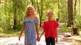 Childre friendship and happy childhood. Two teen girls friends walk in park hold hands look at camera and smile, front view. Teenagers on walking together. Стоковые видеозаписи