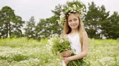 Smiling girl in floral wreath with chamomile bouquet summer field. Portrait girl teenager with flower bouquet posing on camomile field at summer day