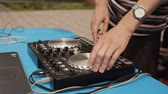 jokey : Close up DJ mixing music on sound console at outdoor party. Disc jockey playing music on controller panel. Mixing deck at summer party