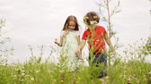 Little boy and girl touching burdock flowers at walk on green summer field. Young brother and sister looking blooming flowers on summer meadow at vacation