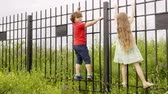 proibir : Little boy and girl climbing on iron fence in countryside. Playful childrens having fun in village at summer vacation Stock Footage