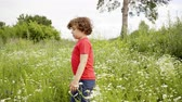 Curly boy walking on flowering field at summer day. Cute little boy walking on grass meadow at summer vacation in countryside