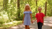 Two Pretty Smile Girls Walk Hold Hands Summer Park. Couple Happy Caucasian Female Children Stroll Asphalt Road Wood Trees Summertime. Leisure Activity Casual Clothes Free Time Holiday Concept