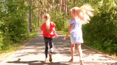 Playful Girls Walk Summer Park Road Hop Back View. Pretty Caucasian Female Friends Blonde Long Hair Stroll Asphalt Way. Joyful Children Throw Pine Cone Outdoor Nature Coniferous Wood Leisure Concept