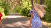 Happy childhood and outdoor activities at summer vacations. Teen girls throw fir cones playing the game together in nature park. Friends ae standing on asphalt walkway. Walking in park. Стоковые видеозаписи