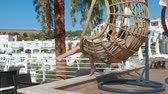houpavý : Carefree girl relaxing in hanging chair cocoon with smartphone in luxury hotel. Girl teenager swinging in cocoon chair with mobile phone at sunny terrace in resort hotel