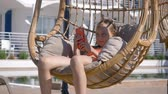 vime : Young girl looking mobile in hanging chair cocoon in resort hotel. Girl teenager swinging in cocoon chair with using smartphone at sunny terrace in resort hotel