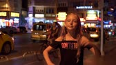 marmaris : Marmaris, Turkey - September 23, 2019: teenager girl dancing on street on moving taxi cars background. Smiling girl dancing on evening street front camera Stock Footage