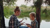 平等 : Teenager girl and boy playing rock paper scissors on river shore in pine woodland. Happy sister and brother playing rock paper scissors in summer forest on river coast 動画素材