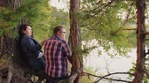 verificador : Back view of middle aged couple sitting and relaxing near river. Rear view of man and woman in checkered shirts sitting on tree roots and talking while relaxing near river in forest Stock Footage